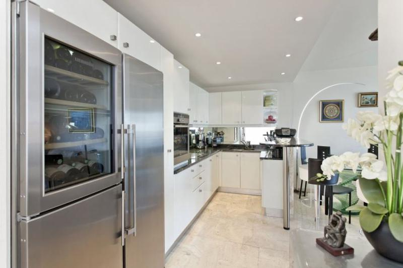 Silver metallic fridge with a wine cellar in a kitchen with white storage cabinets