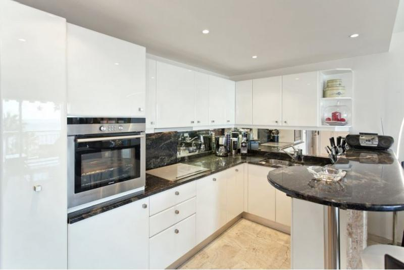 Kitchen with white storage cabinets, a coffee machine, a microwave and black countertops in Cannes
