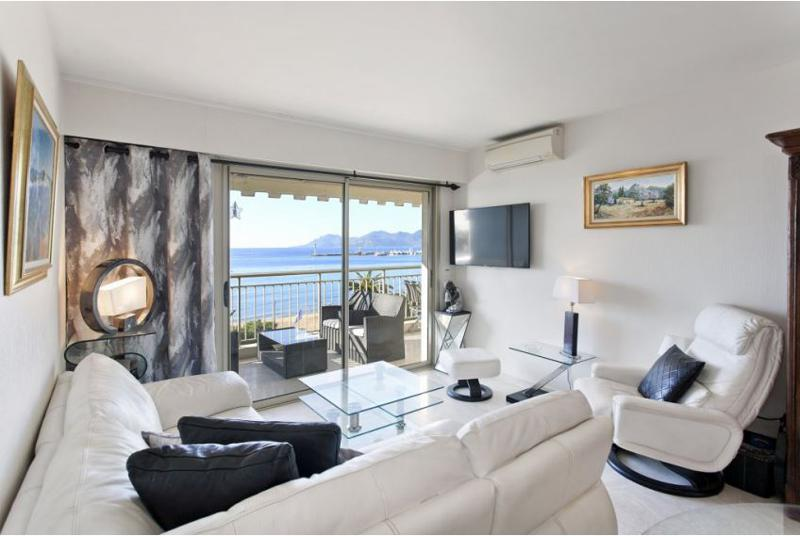 Living room with white couch and interiors, air conditioner, tv and paintings mounted on the walls in Cannes group apartment