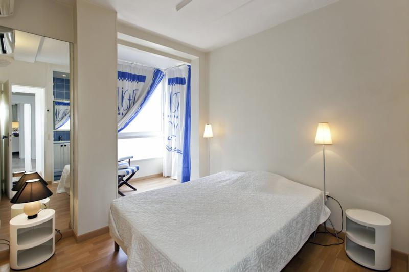 Double bedroom with a white blanket, floor lamps, a chair next to the window with views and an attached bathroom in Cannes
