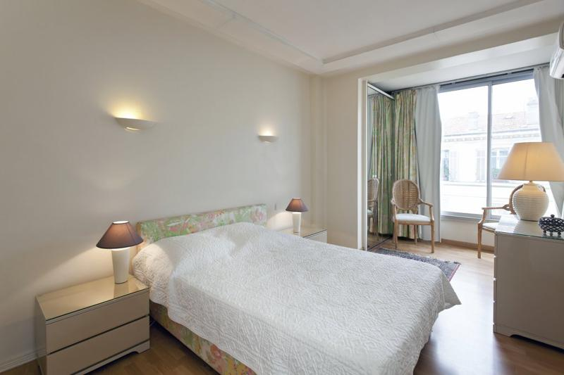 Double bed with side tables and lamps in bedroom with 2 chairs in a seating area and a window in Cannes rental accommodation