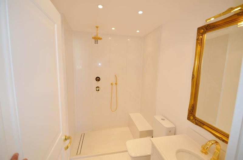 Bathroom with a golden coloured mirror frame, tap, and shower