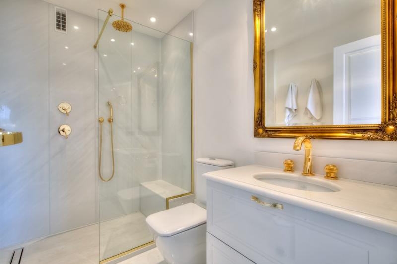 Glass enclosed standing shower in a bathroom with white and golden theme