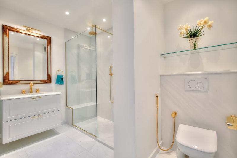 White marble floor in a bathroom with a standing shower and a toilet with a water jet in Cannes rental accommodation