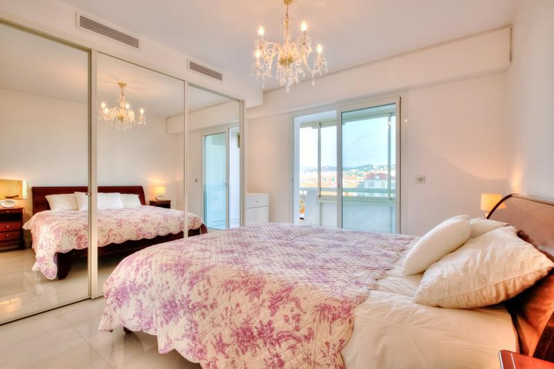 Double bedroom with a full-length closet mirror, white pillows and a private balcony with Cannes views