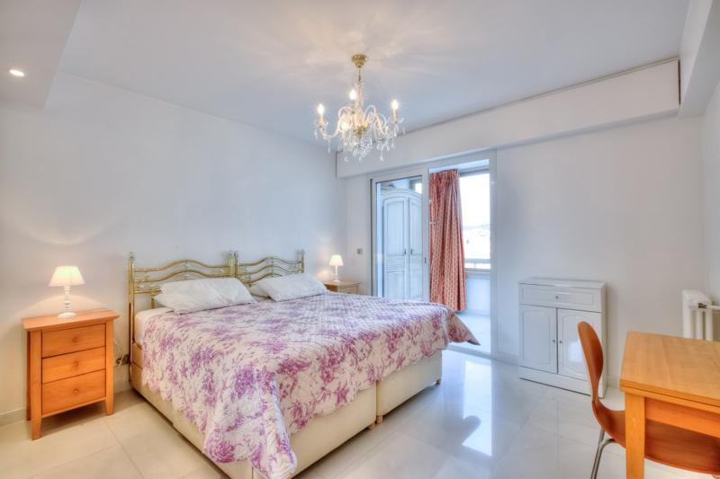 2 single beds, a wooden side table, a desk and a chair in a bedroom with terrace in Cannes