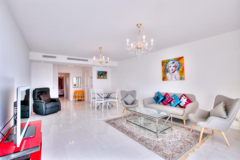 Living room with office space, couch, chairs, tv and a black massage chair  in a Cannes rental apartment near to the Palais