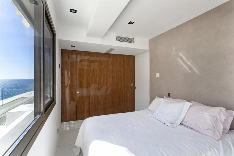 Double bedroom with white sheets and covers and panoramic sea views in Cannes rental penthouse next to Palais des Festivals
