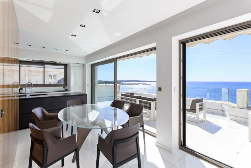 Open kitchen and dining table with brown leather chairs, opening up to a sea facing terrace of a Cannes corporate penthouse