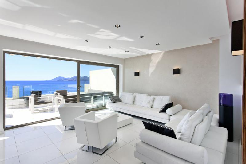 White couch sets and glass doors with views of terrace lounge and sea in the living room of a Cannes group event penthouse