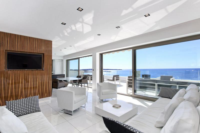 White couches and floor in a Cannes group rental penthouse with a sea facing terrace lounge for Lions on the Croisette