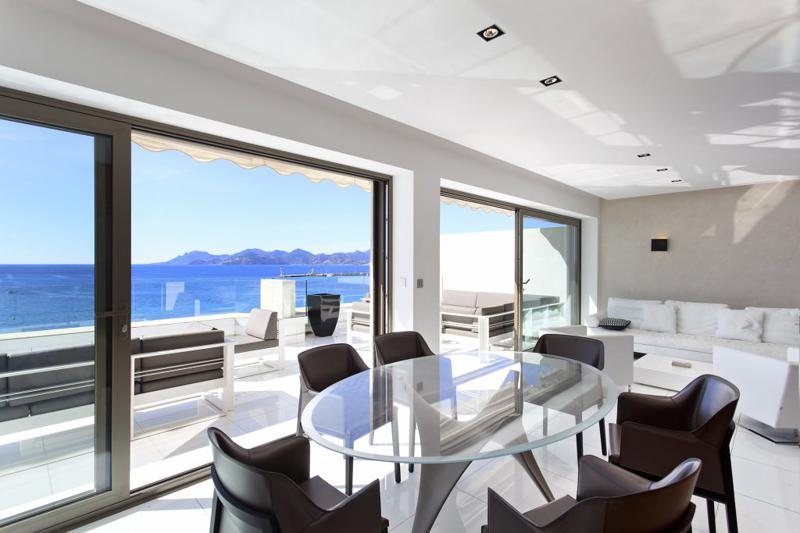 Brown and white couches and chairs on the living room and the terrace with panoramic sea views of a Cannes penthouse for rent