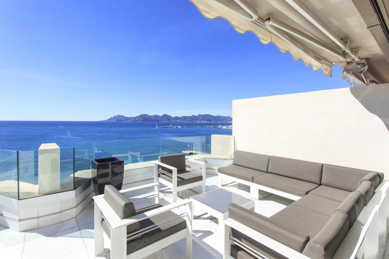 Sectional couch and chairs on the sea facing terrace lounge of a Cannes party penthouse for rent on Boulevard de la Croisette