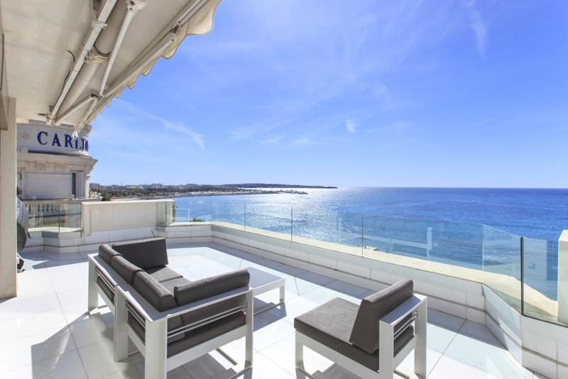 Terrace with couch sets and panoramic sea views in a rental accommodation right next to Hotel Carlton on the Croisette