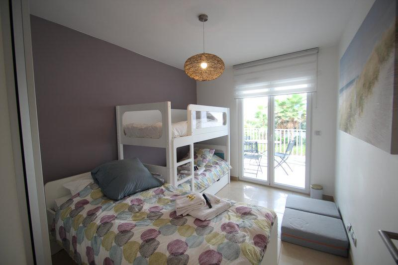 A double bed and 2 bunk beds in a bedroom overlooking a terrace with chairs in a Cannes group accommodation for rent