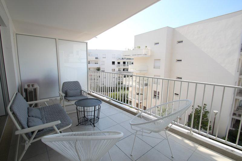Terrace with patio furniture and views of the surrounding buildings in Cannes rental apartment