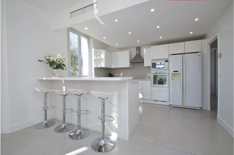 Bar stools on the other side of the kitchen countertop in a Cannes central group accommodation