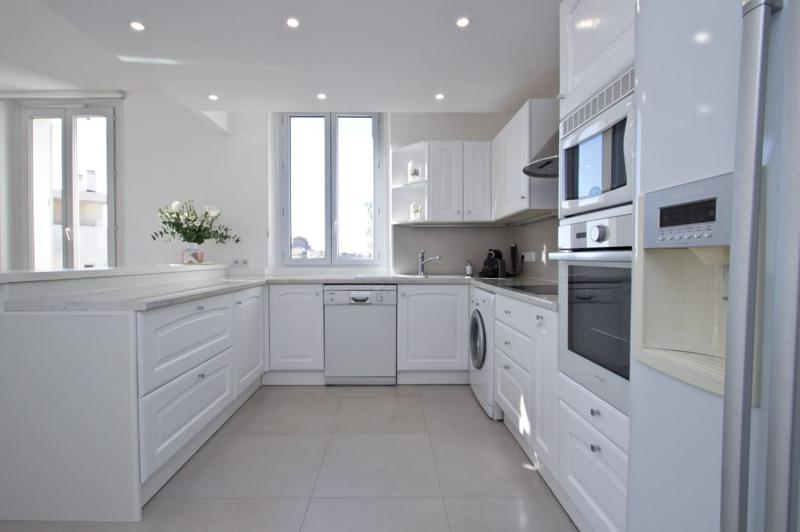 Spacious white themed open kitchen with a dishwasher, a washing machine, a microwave, an oven in a Cannes rental apartment