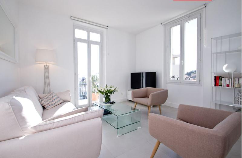 A corner lamp, and a tv in the living room with a couch set and sofas and a door to terrace in a Cannes event accommodation