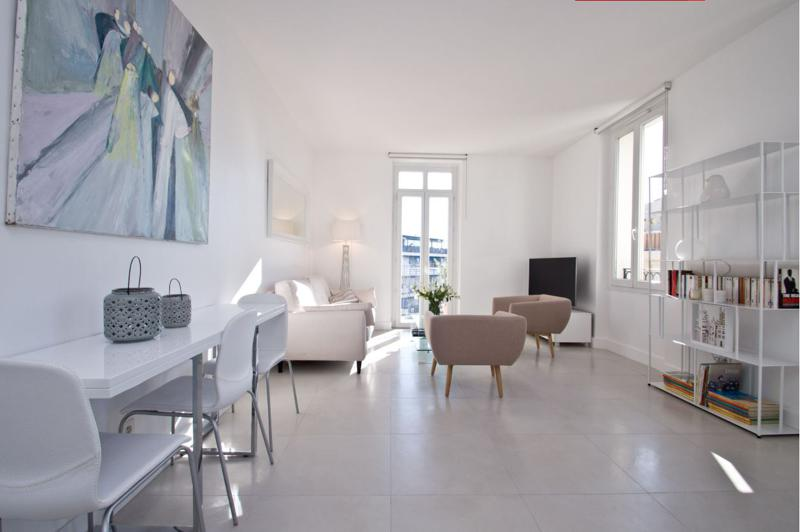 Living room of a 2 bedroom Cannes corporate accommodation with couch sets, tv, table, chairs and a terrace with sea views
