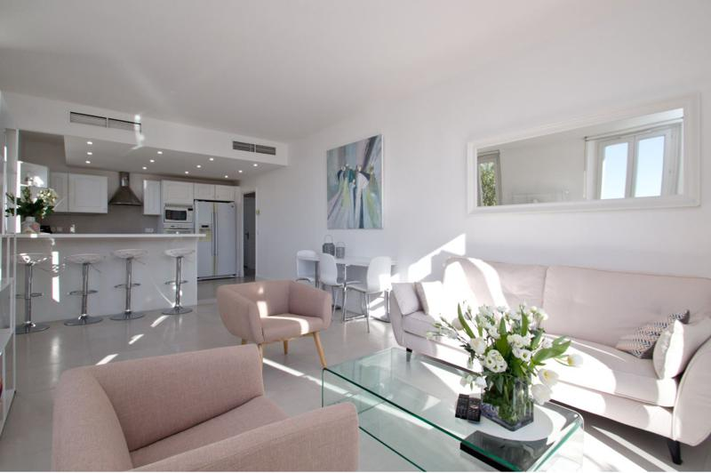 White couch and pink sofas in the living room with open kitchen in a modern Cannes apartment close to Palais des Festivals