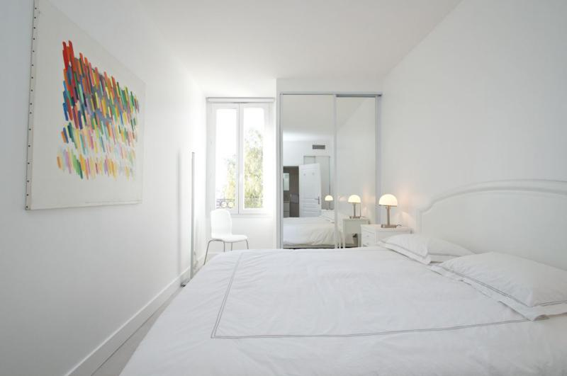 White walls and sheets in the Cannes accommodation's bedroom with natural light and a wall closet