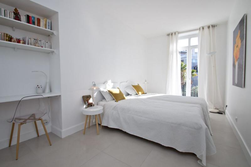 White themed double bedroom with a bookshelf along with a desk and table in a Cannes rental apartment