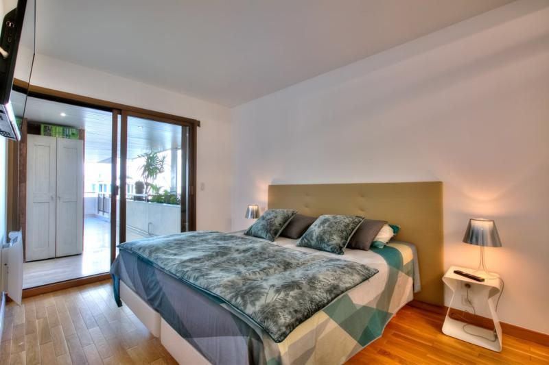 Double bedroom with mustard coloured headboard, white side tables and access to terrace in Cannes event apartment