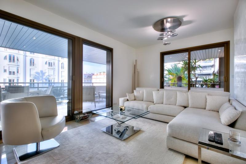 Matching cream couch and rug and a centre glass table in the living room with a terrace in Cannes group accommodation