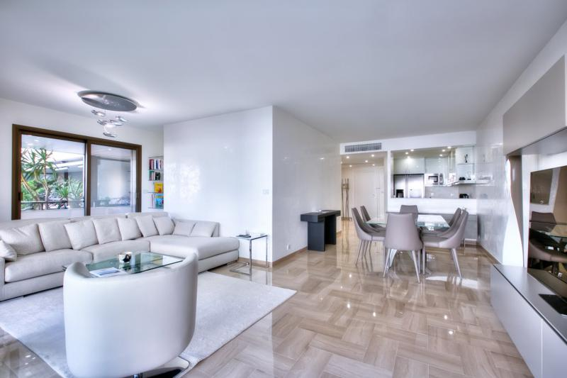 Open dining area and kitchen in the living room with couch, bookshelf and tv of Cannes Event accommodation