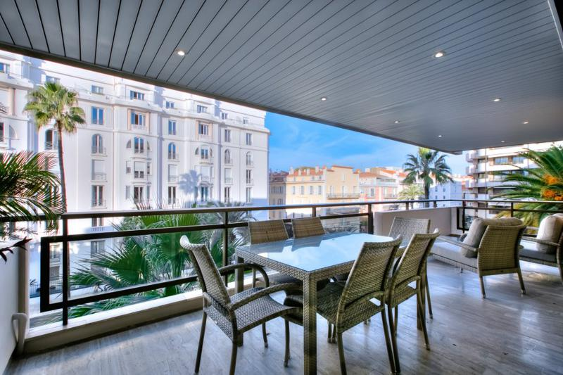 Terrace with roof and a view, relaxing chairs with table in a Cannes group rental apartment