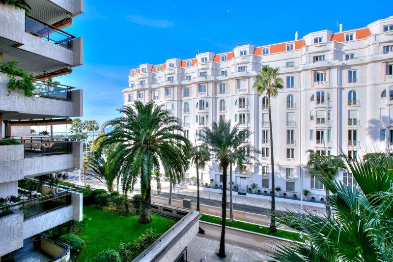 View of palm trees, streets and Gray D'Albion residence from the terrace of a Cannes rental apartment