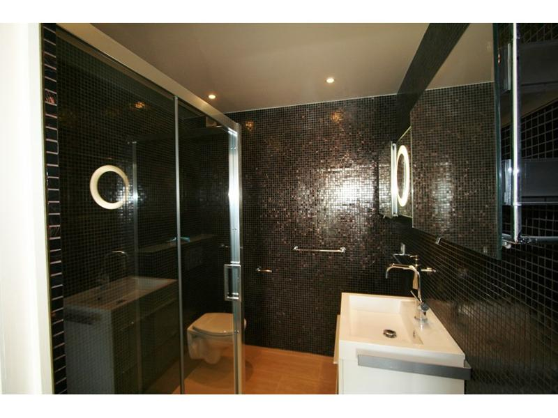 Glass-enclosed standing shower and a white sink in the bathroom with black interiors