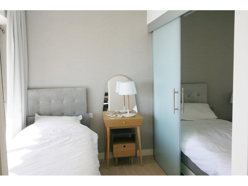 2 single beds with a side table and a sliding door between them in a Cannes sea facing apartment for group events