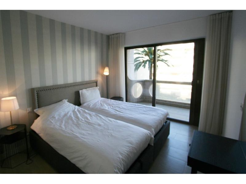 2 single bed with white sheets and pillows in the Cannes bedroom with access to the terrace