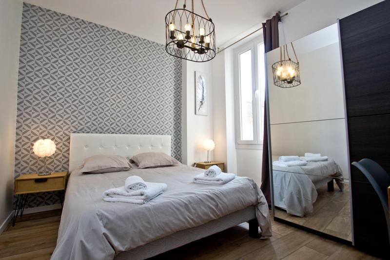 Double bedroom with printed wallpaper, grey sheets with matching pillows and freshly folded towels in Cannes