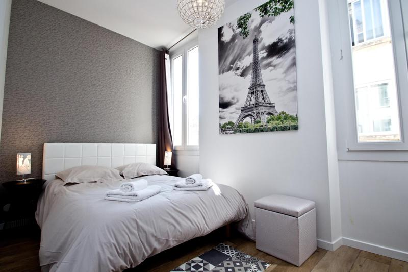 Double bedroom with exterior window, freshly folded towels and poster of Eiffel tower on the wall