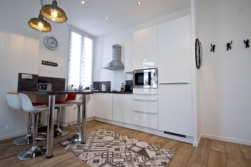 White themed open kitchen with a microwave, coffee maker, a toaster, a bar table with stools in Cannes