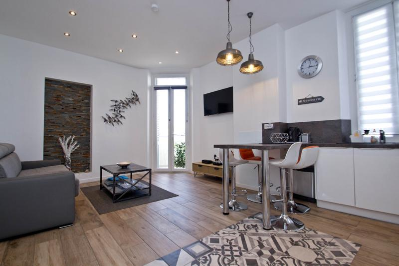 Wooden flooring in the living room with terrace, a couch, a tv, bar table and stools in a Cannes 2 bedroom rental apartment