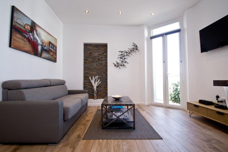 Brown couches placed in front of the tv in a the living room of a Cannes group rental accommodation with terrace views