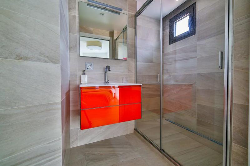 Glass enclosed standing shower and a bright red coloured sink with a mirror in the bathroom