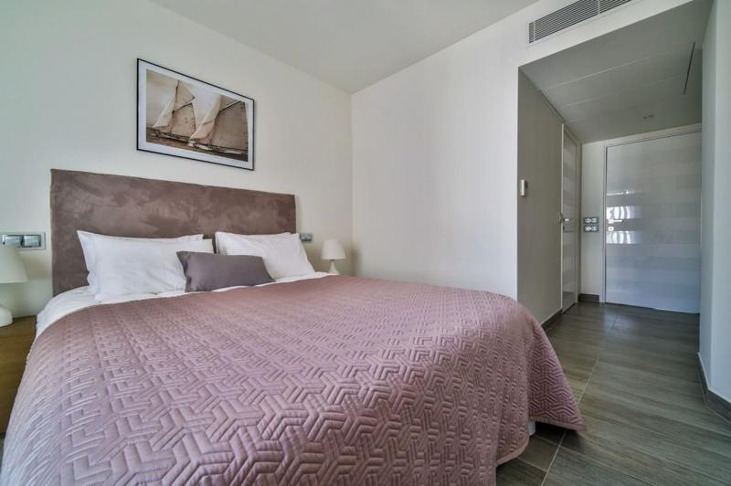 Double bedroom with peach coloured blanket and an attached bathroom in Cannes, near to Palais des Festivals