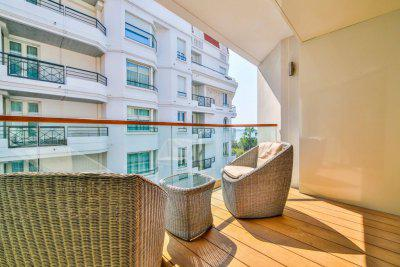 Bamboo chairs and table on the wooden terrace with sea views on the Boulevard de la Croisette in a Cannes group apartment
