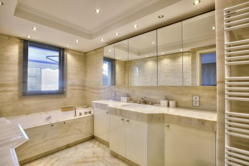 Bathroom with bathtub and mirror cabinets over the sink in Cannes