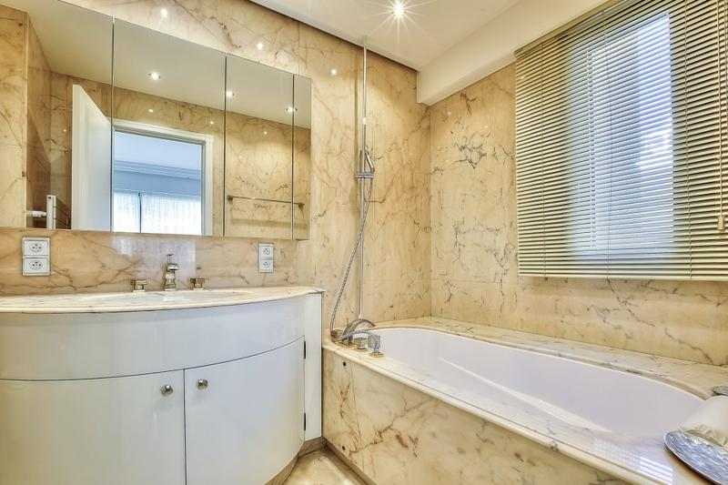 Marble tiles and a window in the bathroom with bathtub