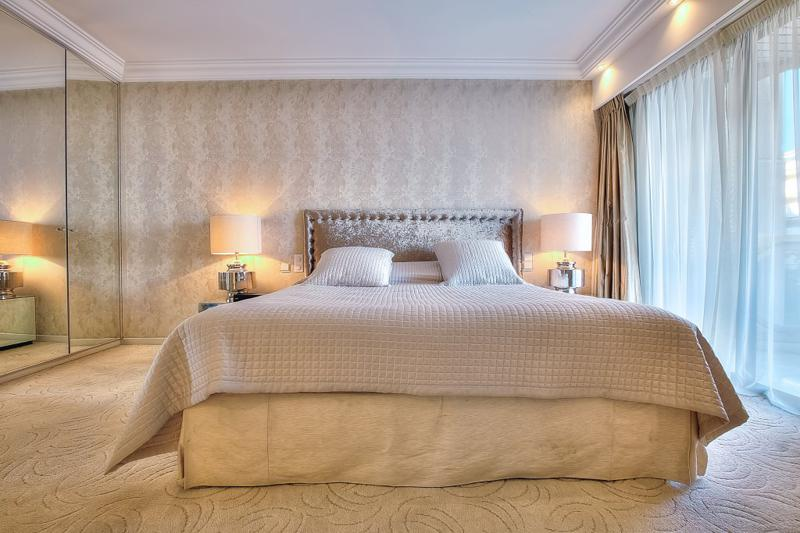Beige coloured theme and matching rug in the bedroom of a Cannes bedroom with access to the terrace
