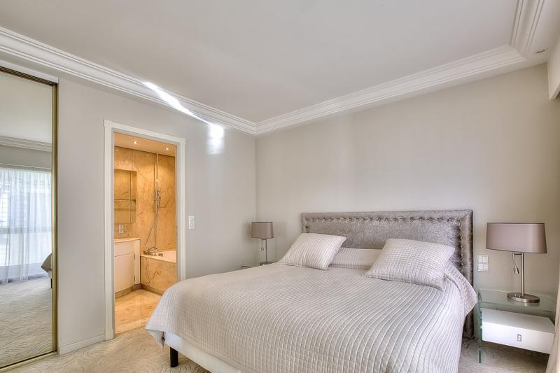 Double bedroom with an attached bathroom with bathtub in a Cannes seafront apartment