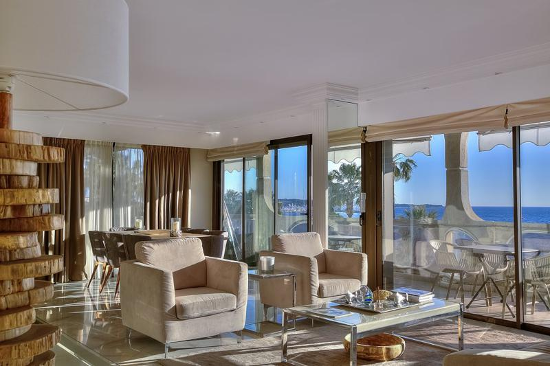 Sofas in the meeting room with glass door walls leading to the sea facing terrace of a Cannes group event accommodation.