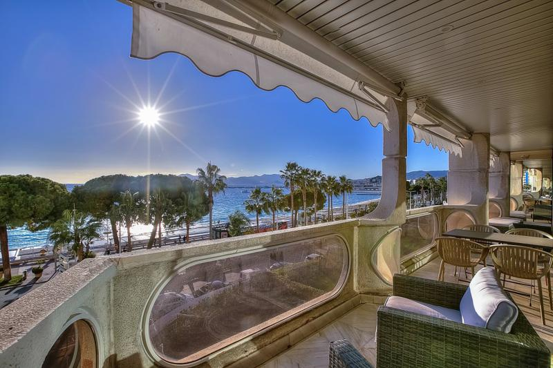 Couches, tables and chairs and sunset views from the terrace of a Cannes seafront party apartment on the Croisette.