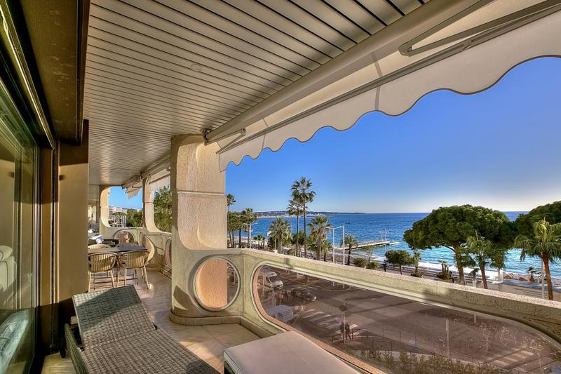 Sea facing terrace lounge with table and lounge chairs in a Cannes rental apartment on the Boulevard de La Croisette.